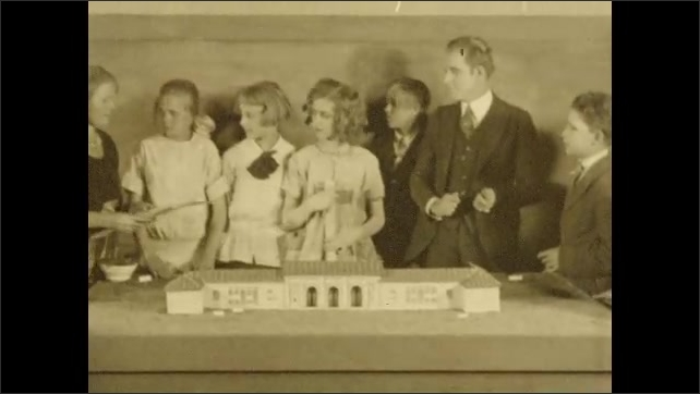 1920s: Teacher places sign for playground in diorama of building on table in classroom. Girl raises hand, points at diorama. Teacher places sign where she pointed. Teacher talks to students.