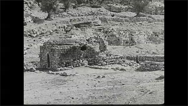 1930s: Woman tends to crippled man on steps. Intertitle card. People walk around ruins. Men stand near camels.