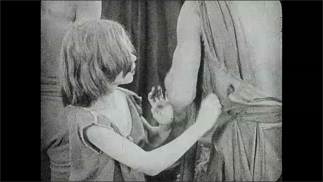 1930s: Blind child feels his way through crowd, bumps into man's crutch, tugs on man's shirt, talks to man, walks away.