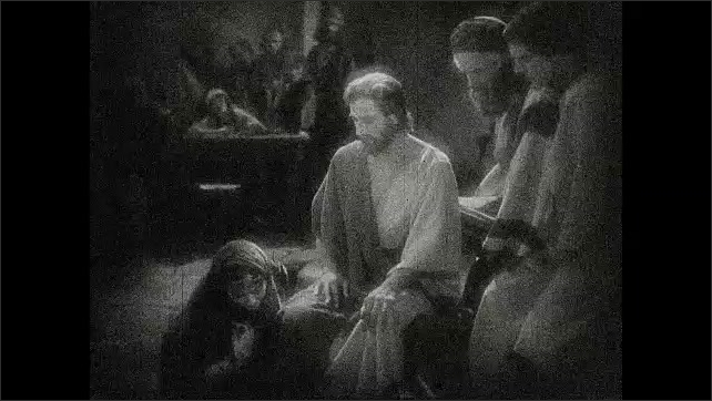 1930s: Woman approaches Jesus, kneels in front of him. Intertitle card. Woman kisses Jesus' robe, Jesus places his hand on woman's head, talks. People watch.