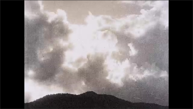 1930s: UNITED STATES: clouds form over hill top. Sun behind clouds. 'When the carry goes west, gude weather is past' title.