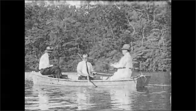 1930s: UNITED STATES: three men go fishing on boat. Close up of terrapin on lake. Man reels in line