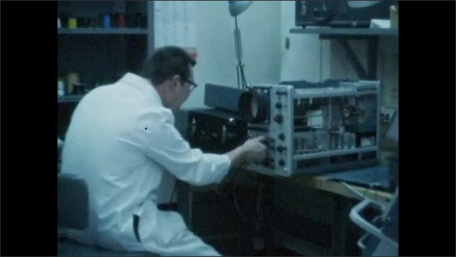 1970s: UNITED STATES: scientist works at machine in lab. Scientist turns knobs on machine