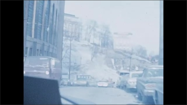 1970s: UNITED STATES: view through window of car driving in city backstreets. Car drives along road. Buildings in city