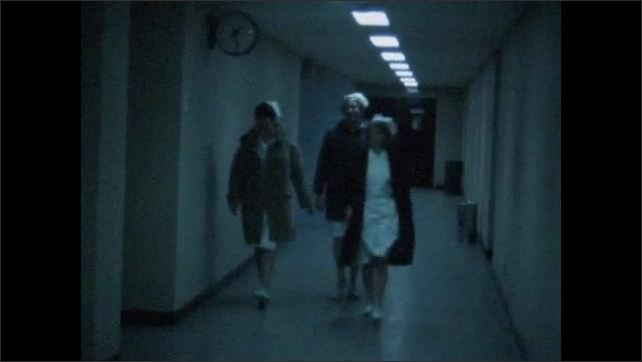 1970s: UNITED STATES: nurses in coats walk along corridor to work.