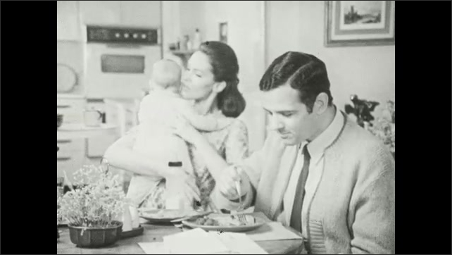 1960s: Baby cries as woman holds bottle to its mouth. Man eats. Woman holds baby. Man stops eating.