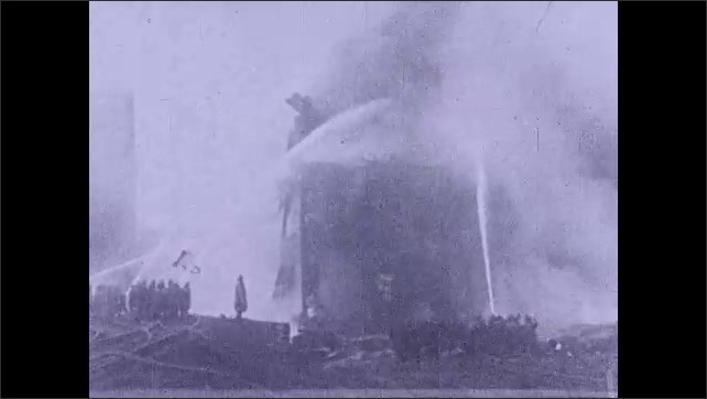 1930s: Firefighters put out fire in building. Water jets put out fire, smoke comes out. Several firefighters put out fire. Intertitle ???? sand blast is driven by compressed air????