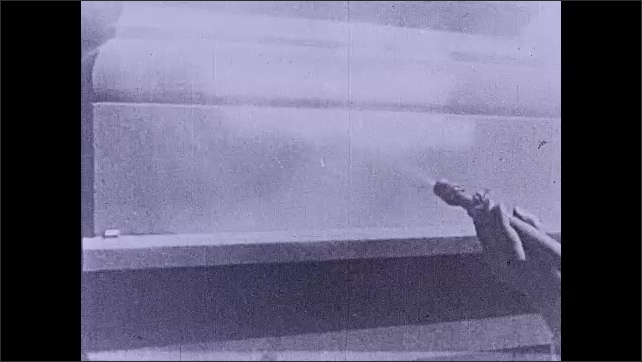 1930s: Facade of a building, smoke comes out from window. An old car is parked on the road. Hand holds hose and sprays it. Intertitle ????ir drives riveting machines????