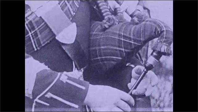 1930s: Intertitle ????he bagpiper uses compressed air???? A man wears a uniform and plays the bagpipes. Hands play the bagpipes. A blacksmith moves a switch next to a stove. Fire.