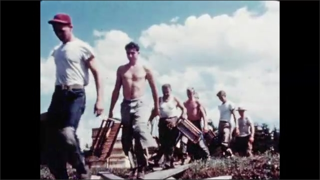 1950s: Men and women walk in line onto cranberry field with harvesting tools in hand. Men and women at work harvesting cranberries in field.