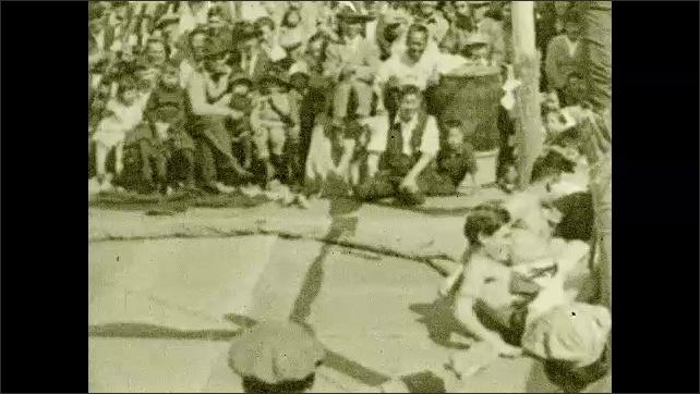1930s: PACIFIC OCEAN: sumo wrestlers entertain passengers on deck of ship. Men wrestle on ship.
