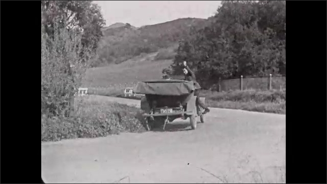1930s: Man runs into street after person on horse.  Man jumps onto side of car.  Woman loses control of horse and falls backward.
