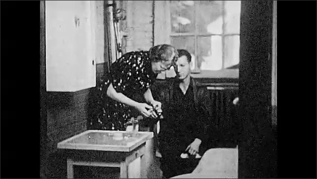 1930s: Dcotor checks the chest of a shirtless man. Woman bandages a mans hand. Man addresses the room.