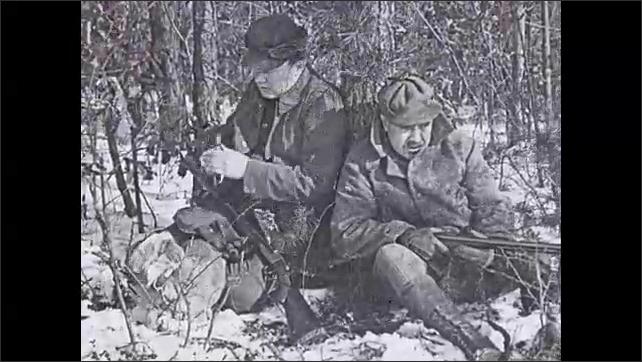 1930s: Men sit in bushes. Intertitle. Men sitting under tree, man blows whistle.
