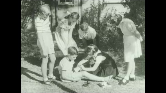 1930s: Spider amongst debris. Boy looks at shoes. Girl ties string around boy's leg as other girls watch. Girl cleans spider bit on boy's foot.