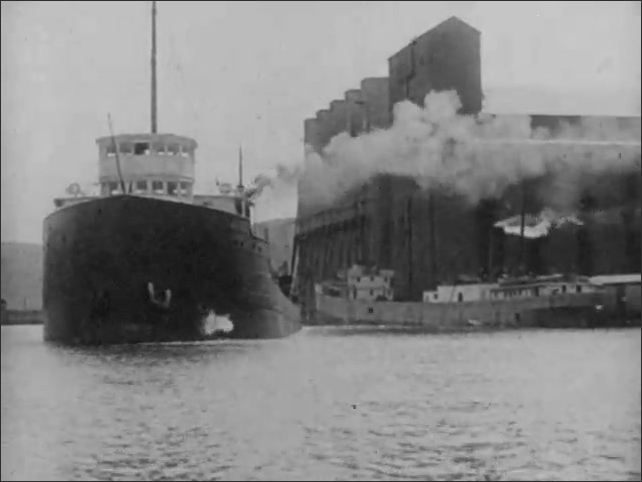 1930s: Grain elevators fill with grain. Ship leaves port. Flatbed train cars carry timber.