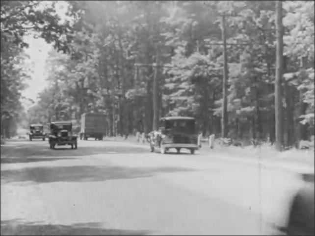 1930s: Prairie grasslands. Passenger train runs through prairie. Cars drive on road through forest.