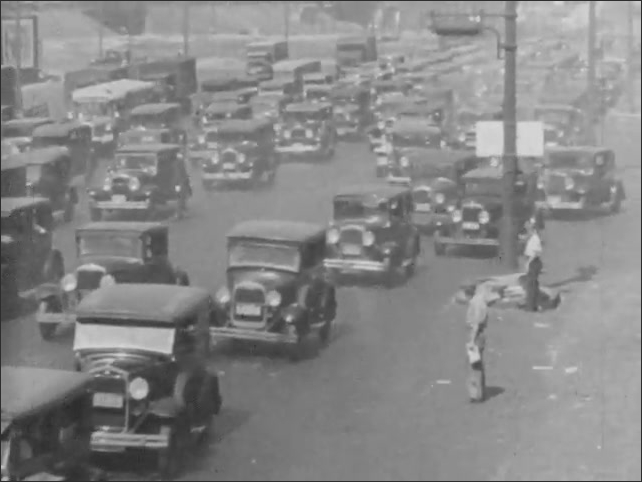 1930s: Ships steam up and down river. Many cars drive and merge on road, traffic cop directs traffic. Cars travel through underground tunnel.