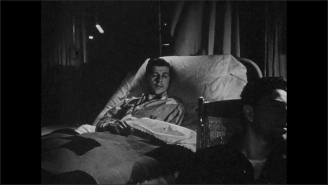 1940s: Men with various amputation lay in hospital beds or sit in wheel chairs, watching flashing screen of projected film.