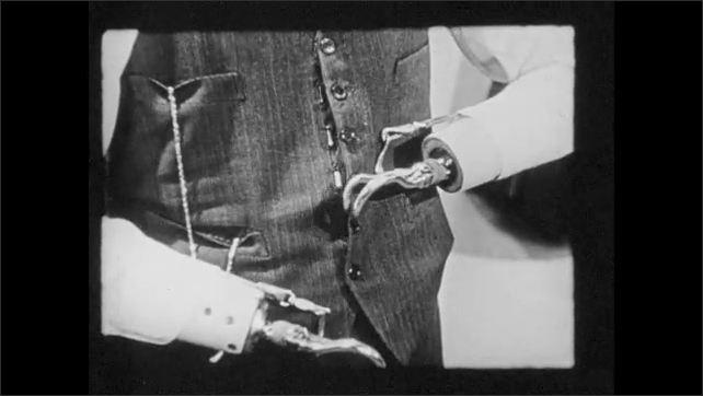 1940s: Man with prosthetic hands puts on dress vest. Man with prosthetic hands puts on vest with decorative buttons (vest held in place with clasps).