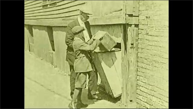 1930s: UNITED STATES: man talks to boy in street. Keep clean and well title. Boy tips rubbish in street bin.