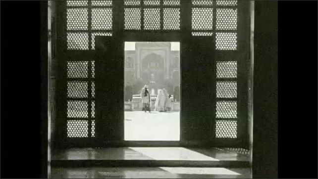 1930s: Men swing bowl on ropes and scoop water from holes and rivers. Man walks outside ornate doorway. Man walks on terrace of Middle Eastern palace.