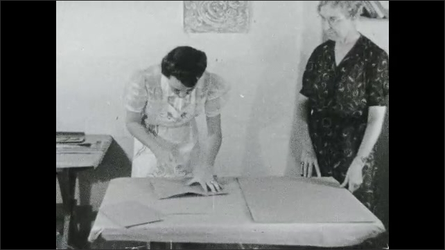 1930s: Text placard. Women fold large papers on table. Woman uses bone folder to crease and fold paper on table, Text placard.