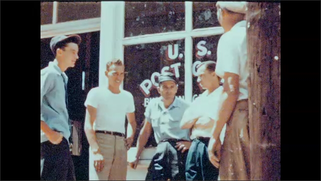 1940s: UNITED STATES: men stand outside post office. Hand opens mail box. Letter in mail box. Bad news received. Letter highlight.
