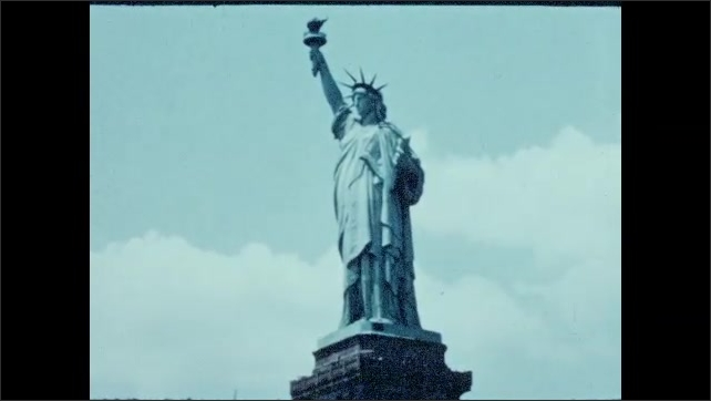 1940s: UNITED STATES: buildings in city. Factories by river in city. Statue of Liberty.