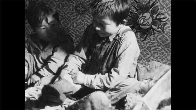 1930s: UNITED STATES: children get dressed. Children put on boots. Children prepare grass for boots