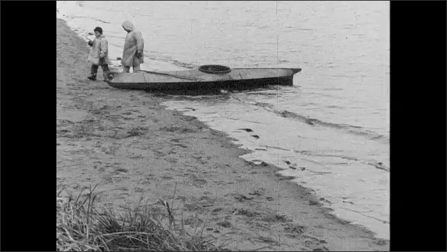 1930s: UNITED STATES: man and boy set out fish nets. Seal skin boat on shore.