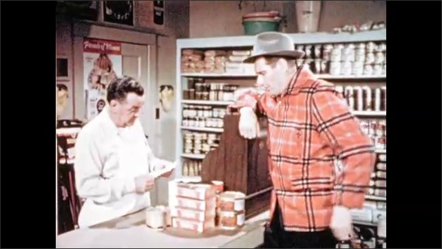 1950s: Grocery clerk looks at list and speaks. Man leans on cash register and listens. Clerk talks and gathers groceries. Man responds and eats  a cookie. Clerk speaks.