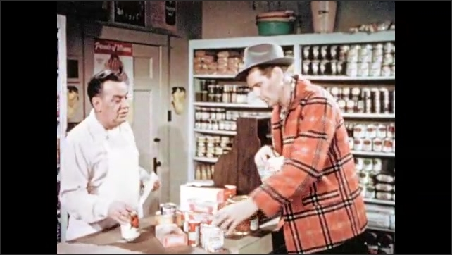 1950s: Man with cookie speaks. Clerk responds and moves around grocery counter. Man leans on cash register and listens. Man and clerk talk over counter.