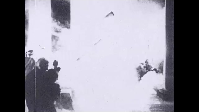 1930s: men and women panic, run around, and fall in room with telescopes as smoke and fire falls from night sky. stars split apart in space and drop downward in patterns.