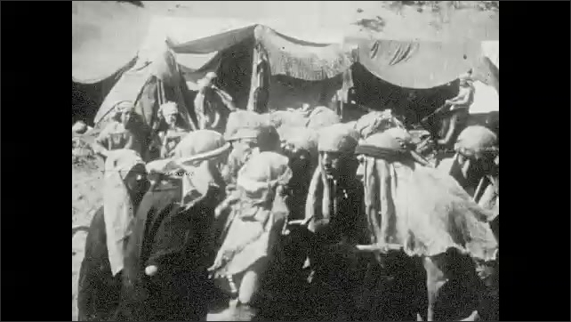 1930s: Words on screen. Men and women in robes and turbans gather and talk near tents.