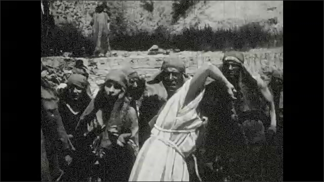 1930s: Moses smashes stone tablets on ground. Crowd recoils in shame. Men and woman hold out their fists and kneel.
