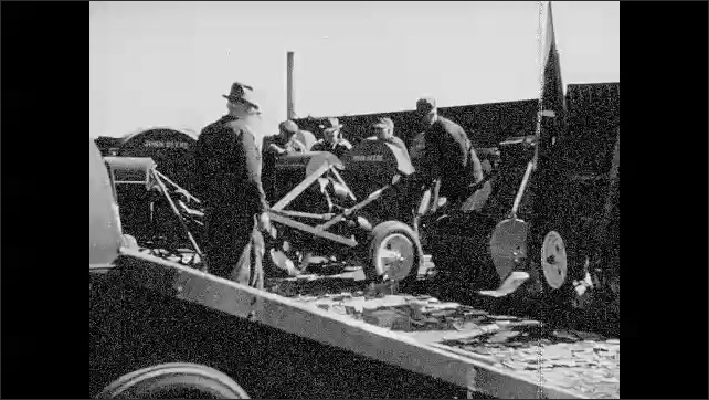 1940s: Man pushes button.  Rope wraps around machine.  Hay is lifted by rope.  Men load machines on truck.  Men build house.