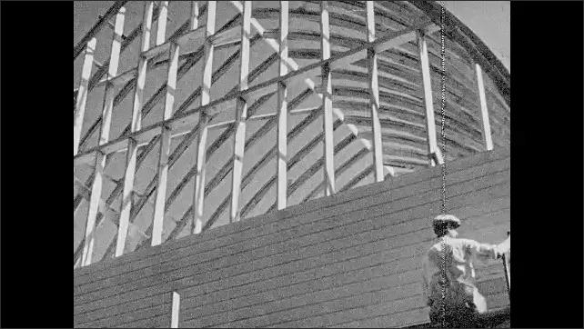 1940s: Schoolhouse.  Man hammers nails.  Man paints building.  Construction site.  Tractor harvests crops.