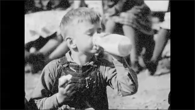 1940s: Crane moves supplies onto ship.  Children sit and eat.  Boy drinks milk.  Crane lowers pallet of boxes.