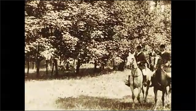 1930s: Man sits on horse back as beagles wait in shade of tree. Man blows horn and beagles emerge from shade. Men ride on horseback through forest accompanied by beagles.