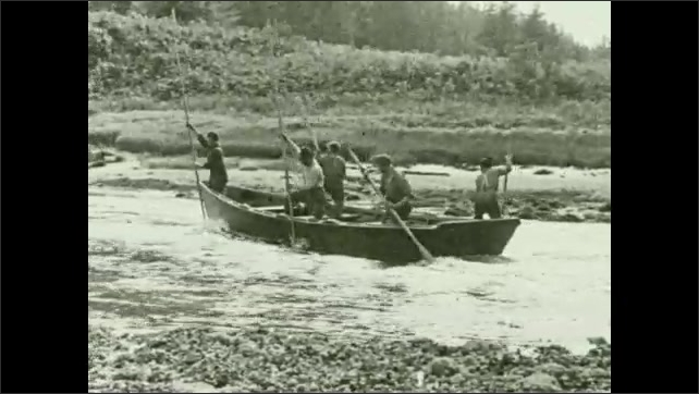 1930s: Men push poles and paddles into water, steer boat down river.