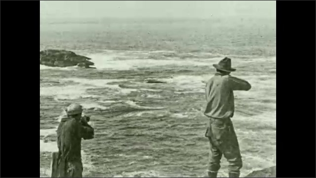 1930s: Men stand on rocks, shoot at sea lions in the ocean.