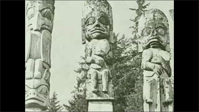 1930s: Man climbs totem pole, sits on top of pole. Man stands under pole, watches. Totem poles.