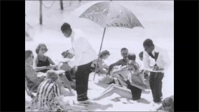 1930s: Intertitle card. People relax on beach. Waiters serve people on beach.