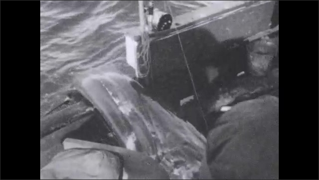 1930s: Man reels in fish. Man pulls marlin into boat. Men sit on back of fishing boat.