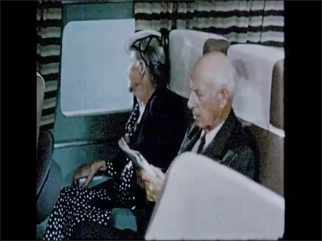 CALIFORNIA 1950s: girl sleeps on plane. Lady covers girl with blanket. View over mountains from plane. Elderly couple look out of plane window