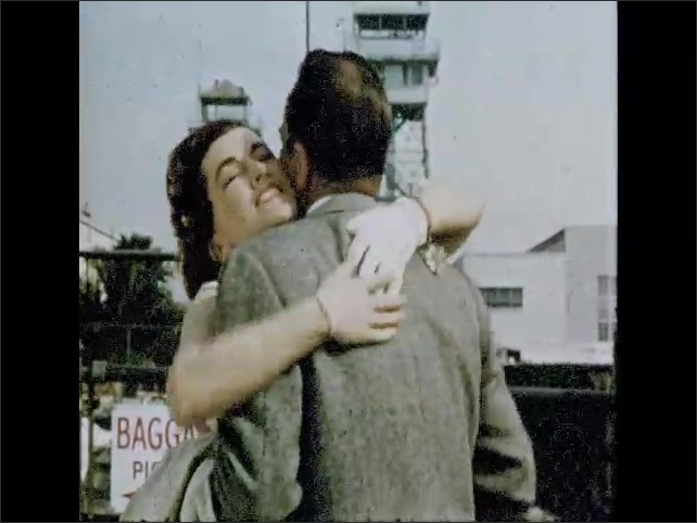 CALIFORNIA 1950s: lady waits in arrivals. Man kisses lady at airport.