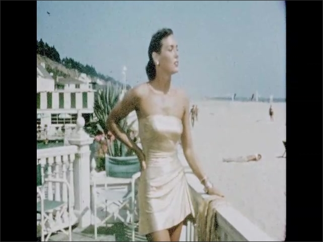 CALIFORNIA 1950s: lady poses by beach. Lady takes off beach robe. Ladies sit on beach. Paramount Pictures studio