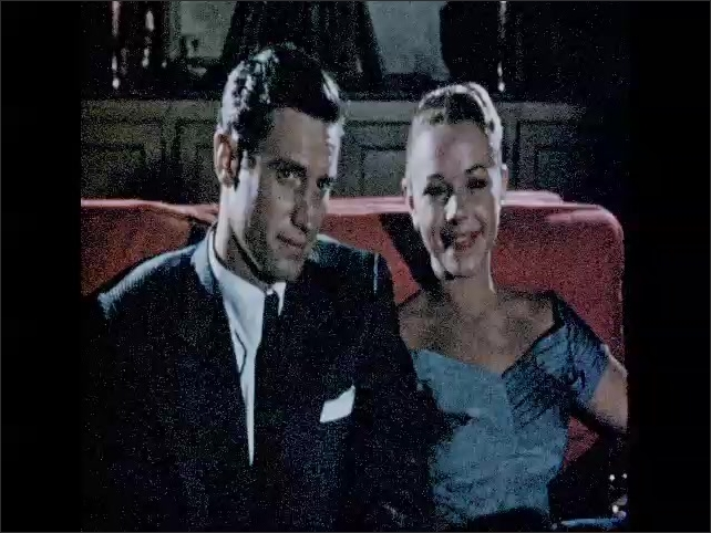 CALIFORNIA 1950s: Couple sit and smile. Lady turns off lights. Palm Springs home movie. Couple watch home movie. Screen credits on film