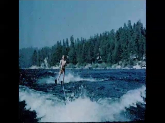 CALIFORNIA 1950s: Lake Arrowhead. View across lake. People sit on boat. Man on water ski. Couples play gold on green